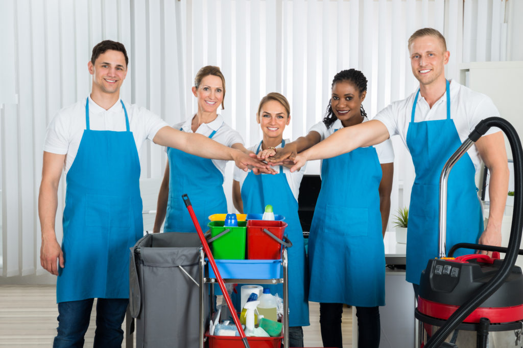 Group Of Happy Cleaners In Uniform Stacking Hands At Workplace